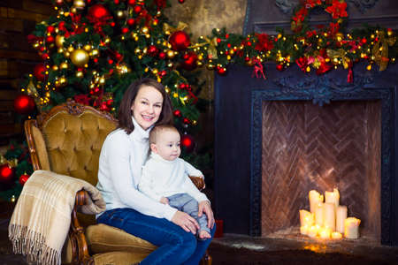 baby near christmas tree: Happy mother with her baby boy siting near the Christmas tree Stock Photo