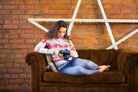 Donna sdraiata sul divano con macchina fotografica Archivio Fotografico - 65241777