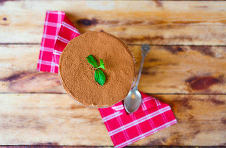 Tiramisu cake in a glass cup on wooden background. Italian mascarpone desert