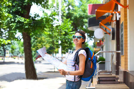 prettiness: Cheerful woman searching direction on location map while traveling abroad in summer, happy female tourist searching road to hotel on atlas in a foreign city during vacation