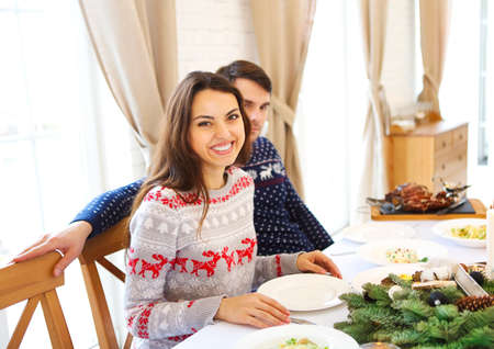 christmastime: Couple of young handsome caucasian man and woman sitting on a table, having christmas meal. Christmas, food, celebration concept Stock Photo