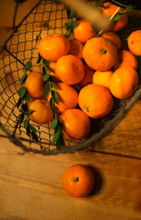 Iron basket of tangerines on a wooden table