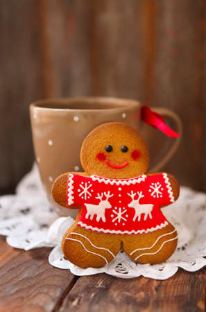 Smiling christmas gingerbread men and tea cup on wooden background.