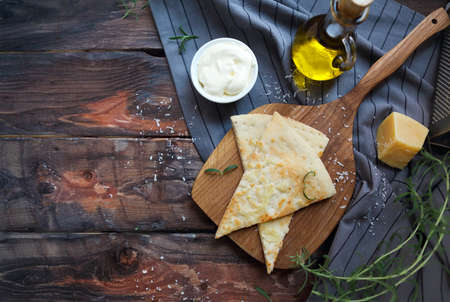 sause: Focaccia with olive oil, parmesan cheese, white sause and rosemary. Homemade traditional Italian bread focaccia on the linen napkin.