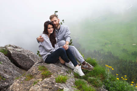 Young loving couple relaxing and hugging, she is smiling and leaning on his shoulder, relationships and feelings concept