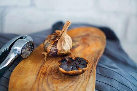 longevity medicine: Black garlic bulbs and cloves on wooden background