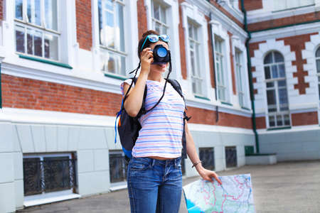 prettiness: Cheerful woman making photo traveling abroad in summer, happy female siteseeing in a foreign city during vacation