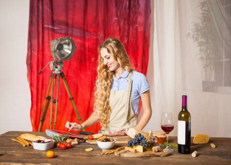 italian cusine: Happy blond woman cooking at the kitchen using tablet computer