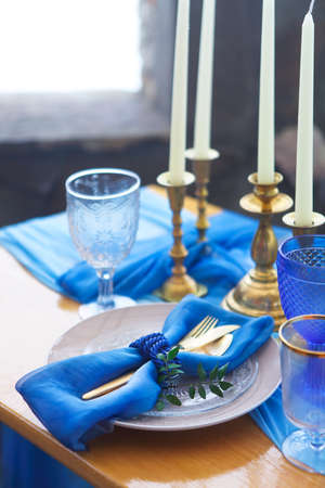 Table setting in vintage style is decorated with candles in golden and blue colors Stock Photo