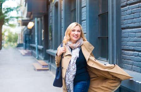Bliski wieku kobieta idzie przez miasto i uśmiechów. koncepcja szczęścia.