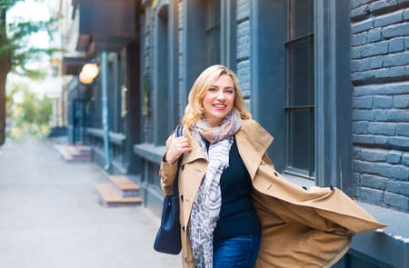 Middle age woman goes through the city and smiles. Happiness concept.
