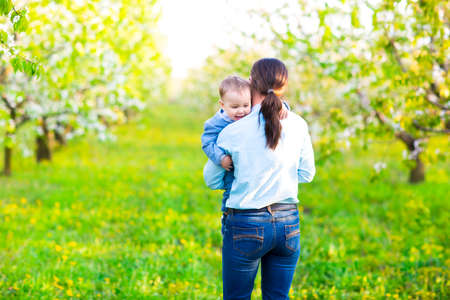 cherry blossoms: Little baby boy with his young mother in the blossoming spring garden