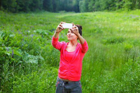 nature photo: Sport woman making photo at mountain forest. Selphie on nature