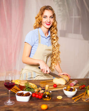 italian cusine: Happy blond woman cooking at the kitchen Stock Photo