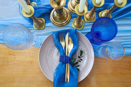 cutleries: Table setting in vintage style is decorated with candles in golden and blue colors Stock Photo