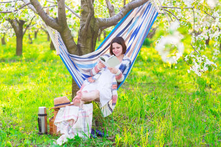 Beautiful pregnant woman sitting in hammock in blooming garden. Lazy time photo