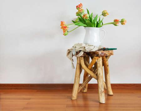 arreglo floral: Todavía vida con el ramo de los tulipanes en el florero blanco en la silla de madera rústica