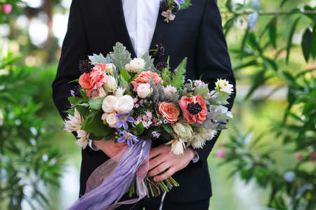 clematis: Groom holding beautiful bouquet in his hands, closeup