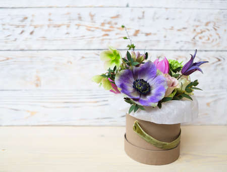 woden: Bouquets of pink and violet flowers in the box on a woden background, close up  Stock Photo