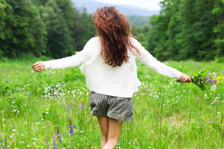 Happy pretty brunette woman in chamomile field, cute female relaxed on flowers meadow, spring nature, having fun outdoor