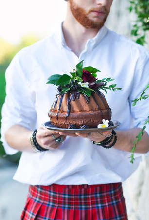 tort: Groom holding chocolate cake decorated with fresh blackberry and flowers oin his hands  Stock Photo