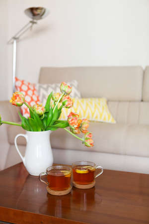 Beautiful orange tulips bouquet with two cups of tea on wooden table in the living room