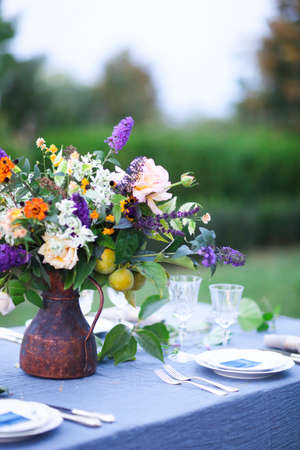 Bouquet of pink, violet and yellow flowers on a table set for dinner, close up