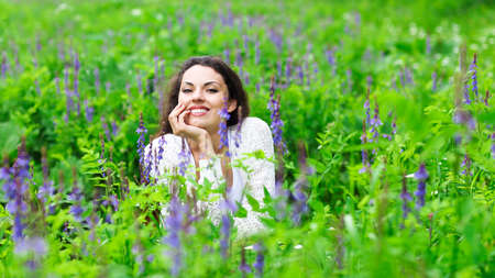 Happy pretty brunette woman in flower field, cute female relaxed on flowers meadow, spring nature, having fun outdoor