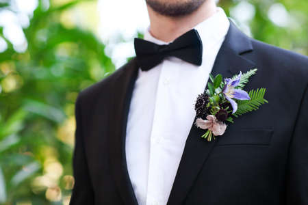 Gentle groom boutonniere with roses, chrysanthemum and beads Stock Photo