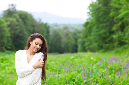 Happy pretty brunette woman in chamomile field, cute female relaxed on flowers meadow, spring nature, having fun outdoor Stock Photo