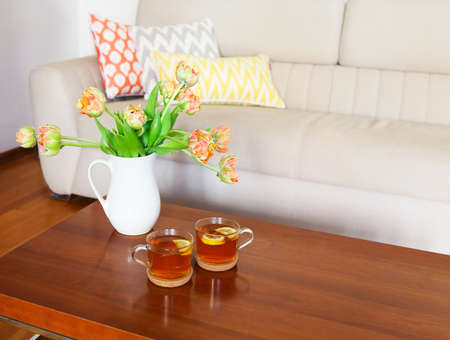 red sofa: Beautiful orange tulips bouquet with two cups of tea on wooden table in the living room