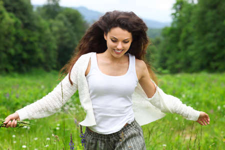 Happy pretty brunette woman in chamomile field, cute female relaxed on flowers meadow, spring nature, having fun outdoor Banco de Imagens