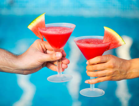 water cooler: People hold watermelon cocktail near pool Stock Photo