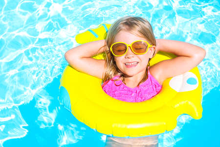 Happy funny child in swimming pool. Girl swim in a pool in an yellow life preserver Stock Photo