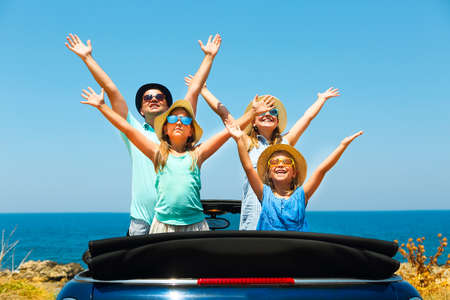 mediterranian: Portrait of a smiling family with two children at beach in the car. Holiday and travel concept