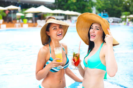 recreate: Happy girls with beverages on summer party near the pool