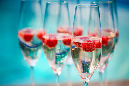Champagne glasses with raspberry. Summer pool party Stock Photo
