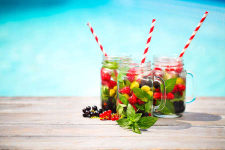 Glass of natural berry lemonade near pool Stock Photo