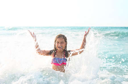 childen: Happy child playing outdoors. Kid having fun in the sea. Summer vacation and travel concept.