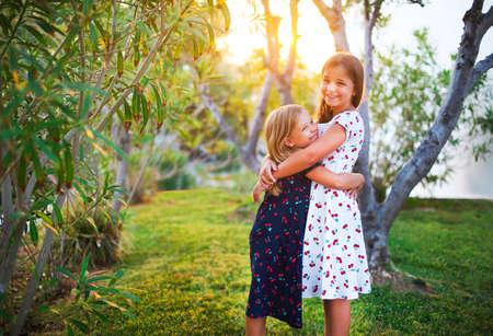 diversión hermanas felices abrazan juntos en tiempo de la puesta del sol