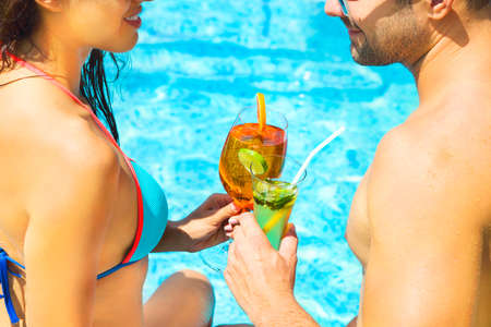 spritz: Young couple are relaxing in swimming pool party. Summer vacation concept