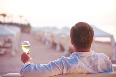 beach view: Relaxing man with glass of white wine on the beach Stock Photo
