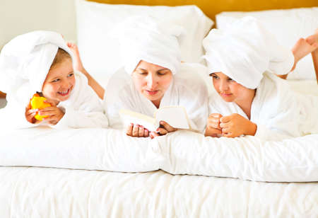 Happy mother and girls in bathrobes in bedroom. Family care and spa concept