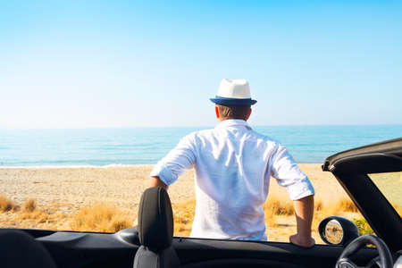 horison: Man on the summer beach near car looking to the sea. Travel and summer vacation concept