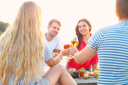 Young friends drinking rose wine on summer beach picnic Stock Photo