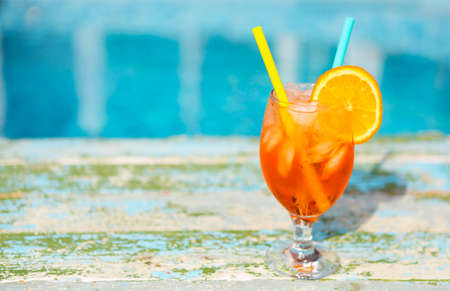Glass of orange cocktail with slice of orange and straw near pool