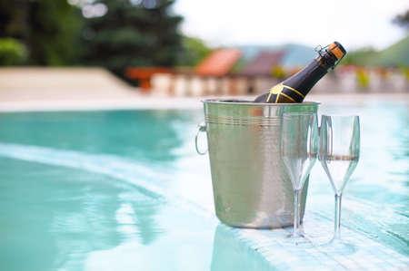 Cubo de hielo botella de champán y dos vasos cerca smimming piscina