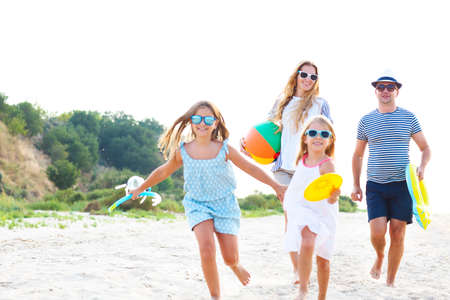 Happy family with children running at the beach photo