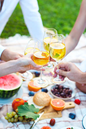 Celebration. People holding glasses of white wine making a toast. Summer party Stok Fotoğraf