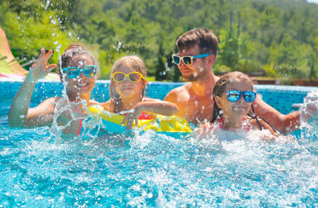 Happy family with two kids having fun in the swimming pool. Summer vacation concept photo